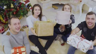Happy young people gives Christmas gifts to camera
