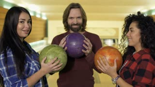 Happy young people with bowling balls