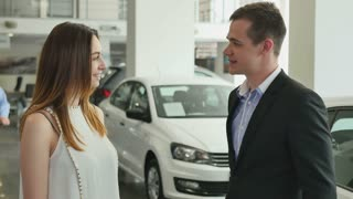 Happy young woman buys a car in car dealership