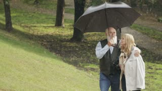 Happy young woman walks with old man under umbrella in park during the rain