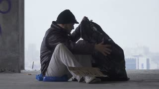 Homeless man goes to sleep on the garbage bag, urban background
