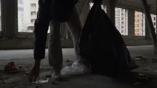 Homeless pick up trash into garbage bag