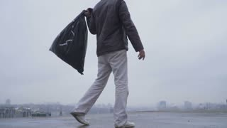 Homeless with garbage bag at the gloomy city background