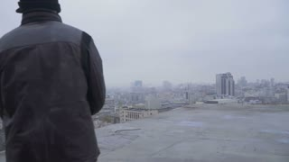 Homeless with garbage bag walks at the roof of abandoned building