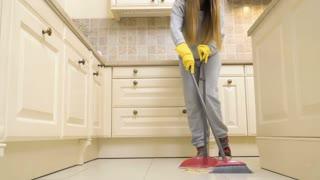 Housewife sweeps the kitchen floor