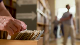 Human fingers on cards catalog in the library
