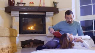 Husband read the book to his wife, happy married couple relaxing near fireplace
