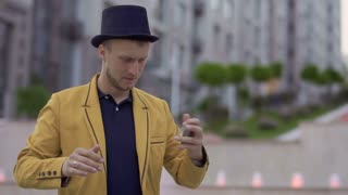 Illusionist in hat and yellow jacket skillfully moving playing cards in hands