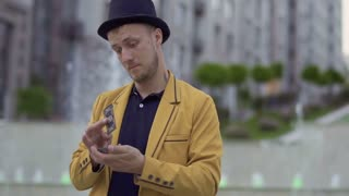Illusionist in hat and yellow jacket with playing cards in hands