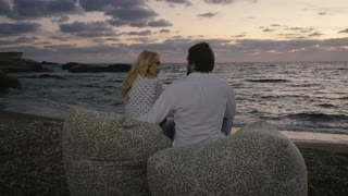 In love couple quarrels on the coast of the evening ocean