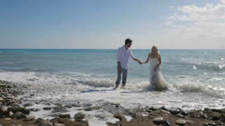 In love newlyweds run away from the waves on the shore