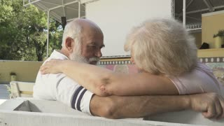 In love old couple has a conversation on the bench in summer cinema