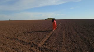 Joyful woman wearing long red dress running at plowed field, aerial shooting