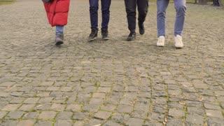 Legs of four people walking