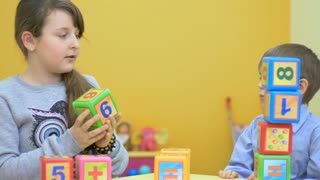 Little boy and girl playing with cubes in the room