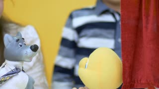 Little boy and girl playing with soft toy in the puppet show in close-up
