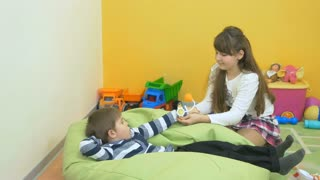 Little boy and girl playing with toy tonometer in the room