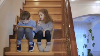 Little boy and girl sits on staircase with tablet