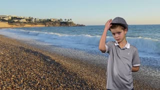 Little boy at sea background take off hat and welcomes