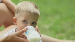 Little boy drinks milk from baby bottle