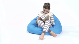 Little boy finish reading book and goes to sleep on bean bag