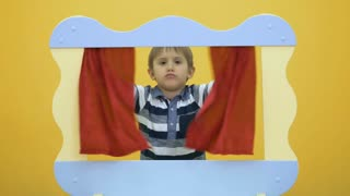 Little boy grimacing behind the screen of puppet show