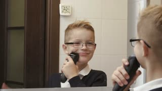 Little boy imitates shaving on face with electric razor