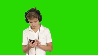 Little boy in big black headphones listens music