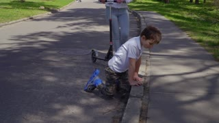Little boy on roller skates rises to his feet after falling on the asphalt
