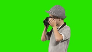 Little boy photographer in hat takes photo at green background