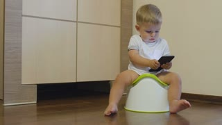 Little boy pisses in his potty and looks at the telephone