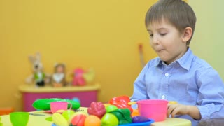 Little boy playing with plastic tableware in children's room