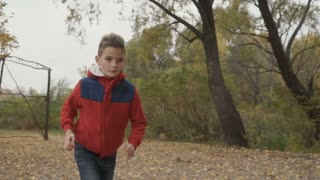 Little boy runs in autumn park