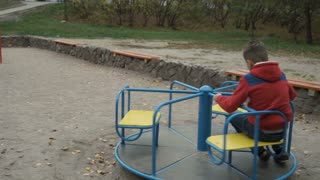 Little boy spinning on a swing at playground