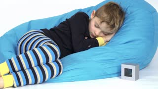 Little boy turn off alarm clock during sleeping