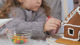 Little children decorates a gingerbread house with a colorful candies
