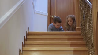 Little children plays near the staircase at home