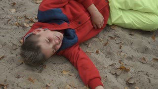 Little crying boy lays on sand