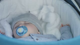 Little cute boy sleeping in the pram