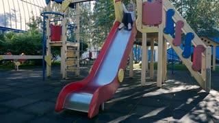 Little girl go down on the children's slide at the playground
