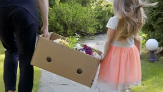 Little girl help her mother to carry cardbox with flowers for seelings