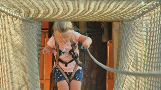Little girl is going through rope tunnel in the park