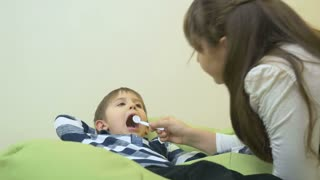 Little girl looking in the boy's mouth with toy medicine equipment