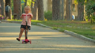 Little girl ride on scooter in park