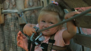Little girl try to overcome obstacles in rope park