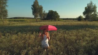 Little girl with red umbrella waves hand and walks on the meadow
