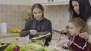 Little girls help mother to cook salad for dinner