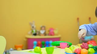 Little kid playing with plastic toys in children's room