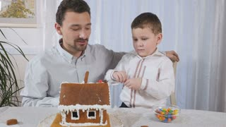 Little son with father decorates a gingerbread house with a colorful candies