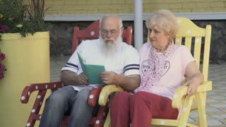 Loved husband reads a book a beautiful wife, old people relax in rocking chairs